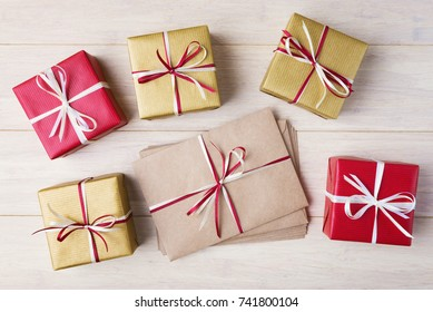 Gift boxes and pile of envelopes on wooden background