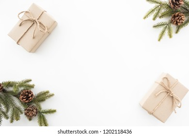 Gift boxes with pine branches and pine cones are on top of white desk table during Christmas or new year. Top view with copy space, flat lay.