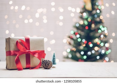 Gift boxes and pine cone on white table over blur christmas tree with colorful bokeh and over bokeh on white background. copy space.