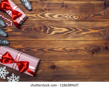 Gift boxes with pine cones, snowflakes and lollypop on wooden board. Holidays concept