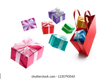 Gift boxes pop out from red shopping bag isolated on white background