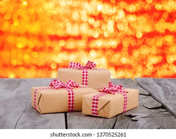 Gift boxes with red checkered ribbon on wooden background