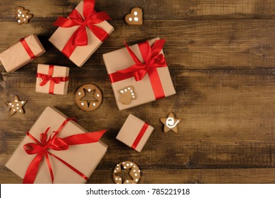 Gift boxes with red ribbon and gingerbread on a wooden surface top view. Surprise in a box with cookies on a wooden background with copy space.