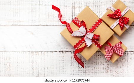 Gift boxes with ribbon on white wooden background. Top view with copy-space