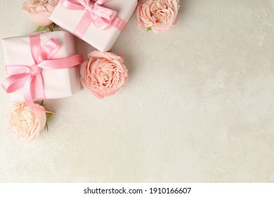 Gift boxes and roses on white textured background, space for text
