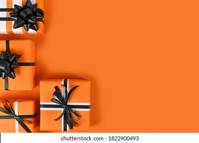 Gift boxes with traditional Halloween colors on left side of  orange background with empty copy space