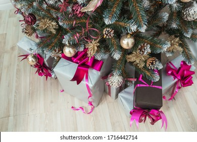 Gift boxes under the Christmas tree with balls ribbons garlands in pink gold maroon style decoration close up. Beautiful Christmas decor. Christmas trees with cones in gold silver glitter sequins.