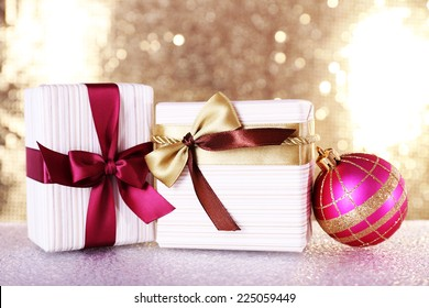 Gift boxes with vinous and golden ribbons and bows and Christmas tree toy on table on shiny background
