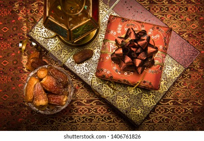 Gift boxes wrapped with decorative wrapping paper placed with traditional Ramadan lamp and a bowl of sweet dates. Eid celebration gift background photo Shot from above.