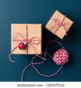 Gift boxes wrapped in kraft paper and tied with candy cane Christmas rope on dark blue background. Holiday concept, top view.