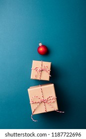 Gift boxes wrapped in kraft paper and tied with candy cane Christmas rope and red Christmas ball on dark blue background. New Year tree concept, top view.