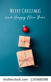 Gift boxes wrapped in kraft paper and tied with candy cane Christmas rope and red Christmas ball on dark blue background. Merry Christmas and Happy New Year card.