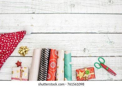 Gift boxes wrapped in red checked paper and the contents of a workspace composed. Different objects on a pink color table. Flat lay. Christmas (xmas) or New year gift packing. Holiday decor concept.