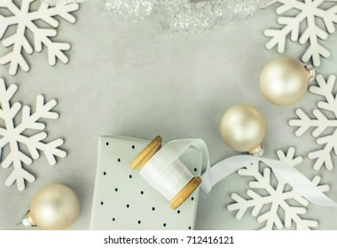 Gift boxes wrapped in silver paper. Wooden spool with white curled silk ribbon, Christmas baubles, snow flakes arranged in frame. Copy space for text. Clean scandinavian minimalist style.