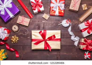 Gift boxes wrapping on a desk with paper rolls, ribbons and scissors, Christmas concept