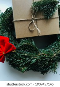 A gift in a cardboard boxe with a wreath and a red bow