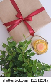 Gift concept Gift box on the table with green pland and candle Birhday Christmas New year Valentine day Top view