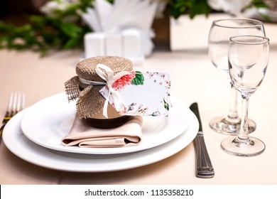 gift confiture decorated with a ribbon and a sackcloth as a present for guests standing at a wedding party table on the plate near glasses. concept of bridal presents
