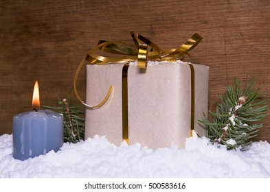 The gift costs in snow. Nearby the burning candle and fir-tree branches.