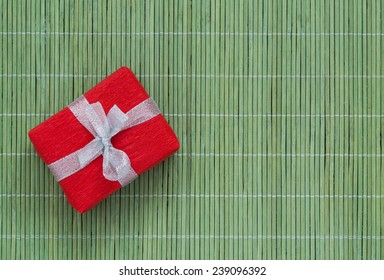 Gift with decorated package on the green bamboo mat Greetings composition with decoratively wrapped gift box on the soft green bamboo background