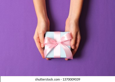 gift in female hands on a colored background top view.