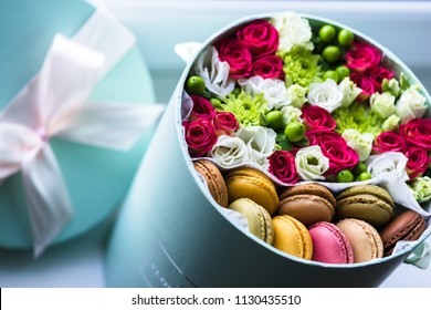 Gift flower box with fresh flowers and macarons.