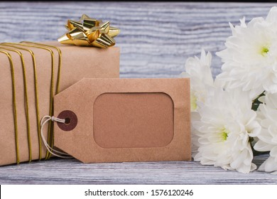 Gift, flowers and decorative carton tag. Holiday background with white flowers, present box and blank cardboard label. Holiday greeting card.