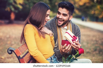 Gift for a girlfriend. Young man surprised his girlfriend with a red rose and present. Love and relationships