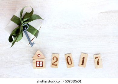 Gift with green ribbon and a small key near layout of the house and numbers / its own property in 2017