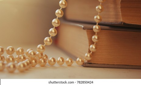 Gift jewelry for women beautiful golden pearls. Beautiful bright rustic background with golden pearls and old books. Precious cute golden pearl beads in soft light. Golden pearls lying on table.
