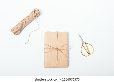 Gift just wrapped in brown eco paper near twine coil and golden scissors, top view. Flat lay composition of handmade packaged present on white table.
