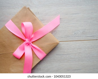 Gift kraft envelope with a ribbon on a wood background