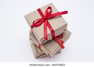 Gift kraft square box with a red ribbon on a white background