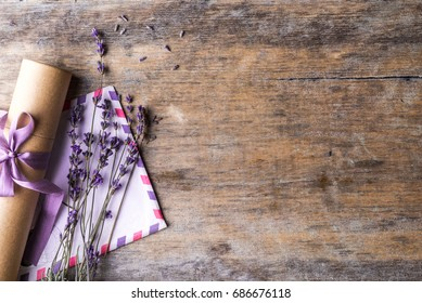Gift and letter with a lavender sprig on an old wooden background. Top view.