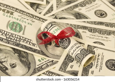 Gift of money with red ribbon on money american hundred dollar bills