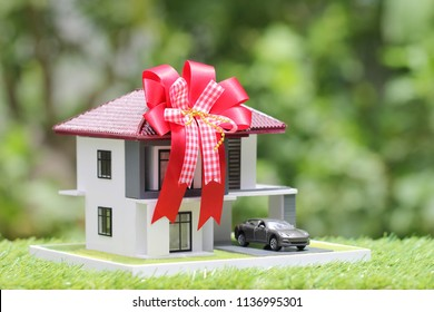 Gift new home and Real estate concept,Model house with Red ribbon and the car on natural green background