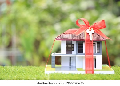Gift new home and Real estate concept,Model house with Red ribbon on natural green background