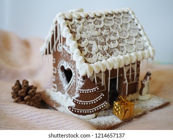 A gift next to a gingerbread house, christmas scenery