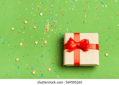 A gift on a festive greenery background. Surprise your loved one. The concept of the St. Valentine's day, weddings, engagements, Mother's Day, birthday, New Year, Christmas and other holidays.Flat fly