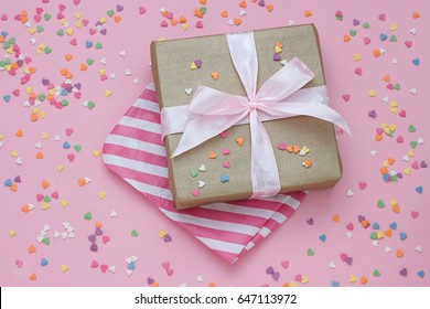 Gift on pink background with little hearts