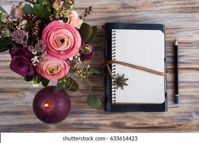Gift, open notebook and flower decor on wooden background. Top view, flat lay with candle and leaves