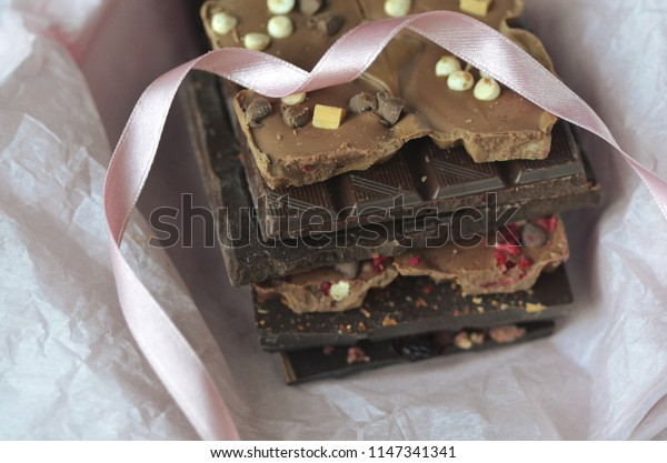 A gift pack of artisan handmade chocolate. Chocolate bars with dried fruit in pink tissue paper on dark background.