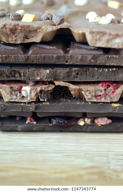 A gift pack of artisan handmade chocolate. Chocolate bars with dried fruiton dark background, front  close up view.