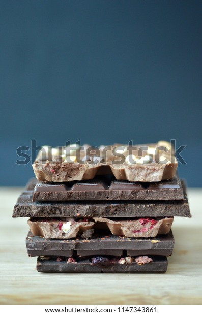 A gift pack of artisan handmade chocolate. Chocolate bars with dried fruit on dark background, front close up view.