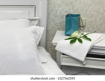 Gift package and fresh white rose on a white bedside table near a white wooden bed covered with white linens.