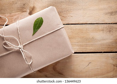 gift package wrapped with paper and rope with a leaf on wooden background