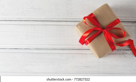 gift packaged in a Kraft paper on a white wooden table with red bow