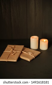 Gift packages in kraft paper and two candles with black background