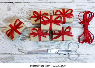 gift packages wrapped in gray paper with organic red ribbon, scissors on the wooden background;