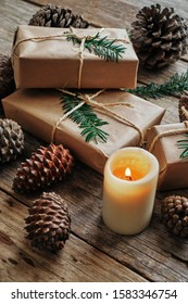 Gift packages wrapped with kraft paper, and surrounded by pine cones and a candle